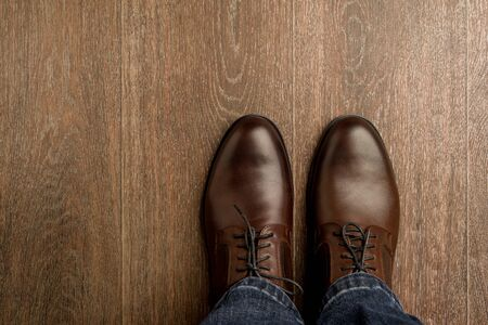 The man wears brown classic shoes on wooden flour. - image