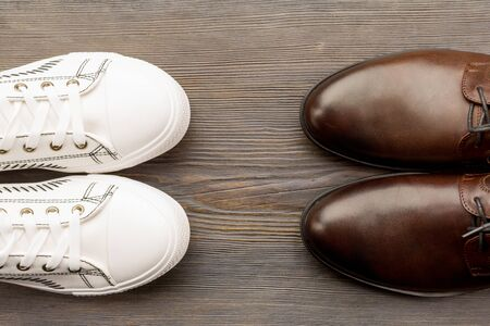 Mens classic brown shoes and white sneakers on a wooden background. Top view - image Stockfoto