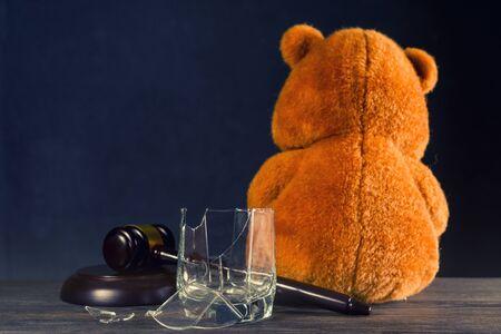 Teddy bear, judges hammer, broken glass. The concept of deprivation of parental rights or divorce due to alcoholism. - image