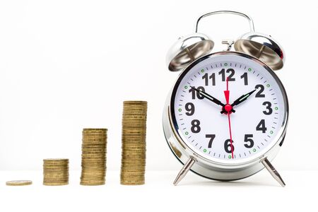 Retro alarm clock and coins stack . Retirement planning. money saving and Investment. White background Banque d'images