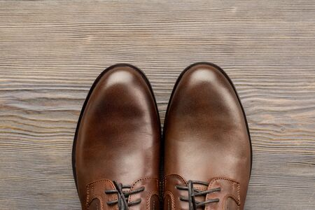 Fashionable men's classic brown shoes on a wooden background - image