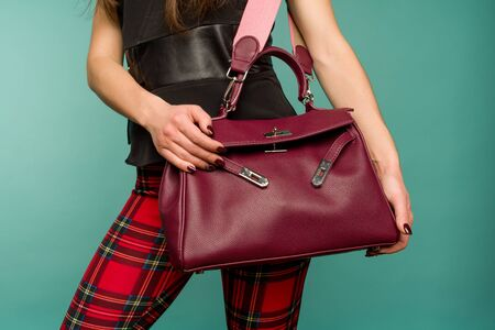 Beauty and fashion. Stylish fashionable woman wearing in plaid pants holding burgundy color bag handbag, studio shot on blue background Standard-Bild - 143297738