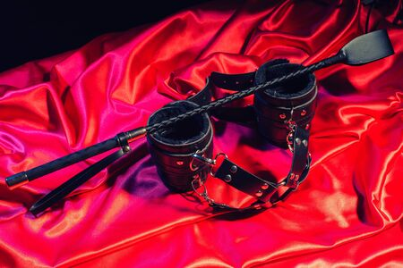 Top view of bdsm outfit. Bondage and spank on the red linen. Adult sex games.