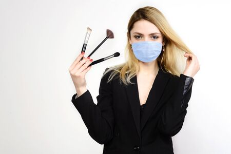 Attractive blonde Make-up artist in mask holding brushes on white background, Coronavirus Outbreak Defense Concept
