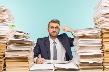 Shocked businessman sitting at the table with many papers in office, he is overloaded with work - image