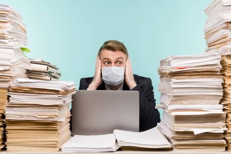 A male accountant or company manager works in an office in a pandemic in view of the accumulated paper work. A protective medical mask is on the face. On the desktop are large stacks of documents. - image