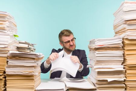 Business executive working in the office and piles of paperwork, he is overloaded with work. Breaks a paper contract and quits his job - image