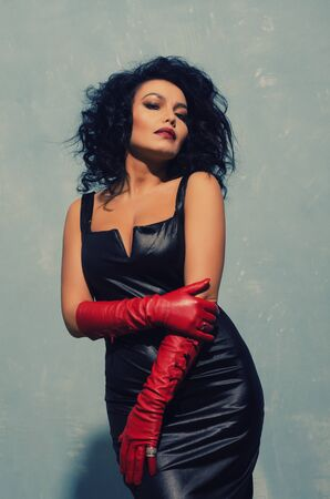 Luxurious Asian woman posing in black leather dress and red gloves. Dominant Fetish Lady. - image Standard-Bild