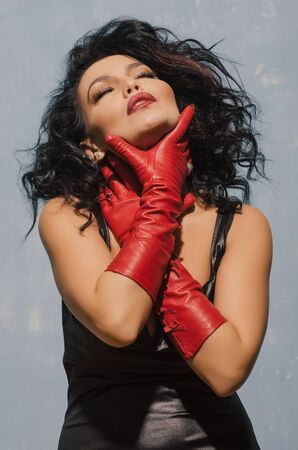Luxurious Asian woman in black leather dress and red gloves holding herself by the throat. Dominant Fetish Lady. - image
