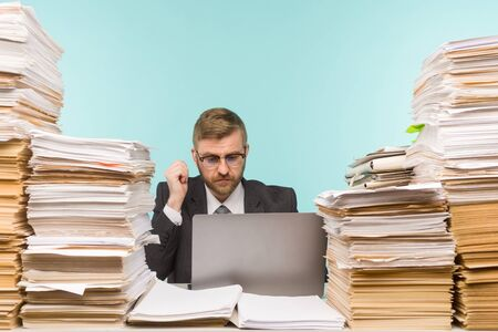 Business executive holds a video conference in the office and piles of paperwork, he is overloaded with work - image