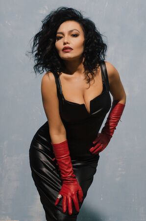 Lujosa mujer asiática posando en vestido de cuero negro y guantes rojos. Señora dominante del fetiche. - imagen Foto de archivo