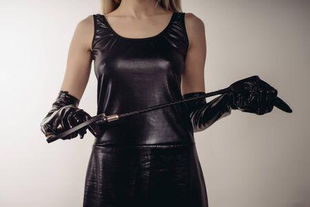 Femme sexy tenant une cravache d'équitation à tête large et à manche court en cuir strict - image