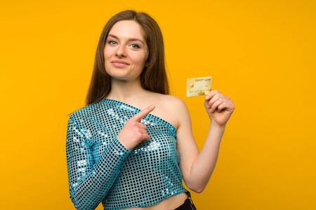 Photo of pleased young woman posing isolated over yellow wall background holding debit or credit card. Standard-Bild