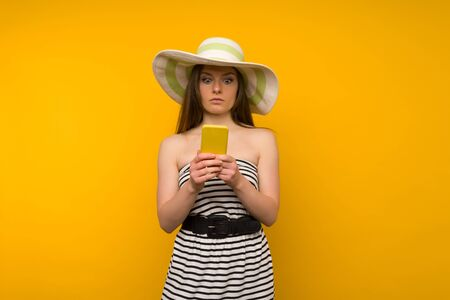 Girl wears straw hat and short white strips dress with open shoulders surprised by the news on a smartphone - image
