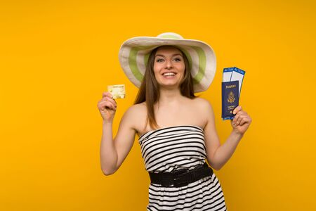 Joyful young woman in a straw hat and a striped dress is holding airline tickets with a passport and a credit card on a yellow background. Rejoices in the resumption of tourism after the coronovirus pandemic. Standard-Bild