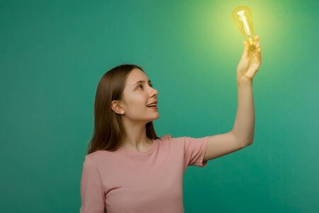Cute girl student looking the lamp in her hand isolated on a background. The concept of an idea or creative insight.
