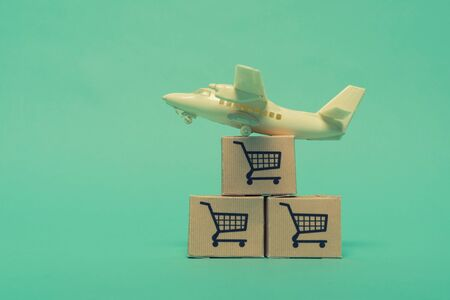 White model airplane lands on blue background from most famous countries around the world with boxes of goods behind. An idea of air freight transportation, global parcel forwarding, international shipping