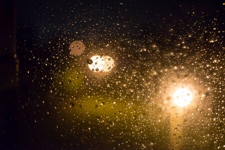 Drops of rain on window glass, lanterns in the background -image Standard-Bild - 150222675