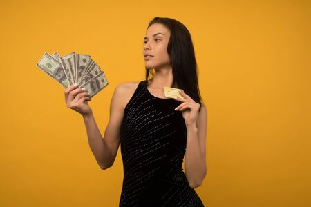 Photo of pleased happy young woman posing isolated over yellow wall background holding money and credit or debt card. - image Standard-Bild