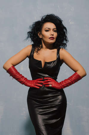 Luxurious Asian woman posing in black leather dress and red gloves. Dominant Fetish Lady. - image Foto de archivo