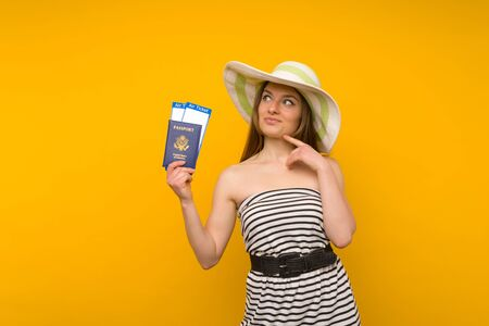 Joyful young woman in a straw hat and a striped dress is holding airline tickets with a passport on a yellow background. Rejoices in the resumption of tourism after the coronovirus pandemic.