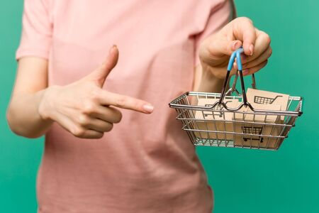 Close up of female hand horizontal holds toy metal shopping basket with blue plastic handle isolated on background. image