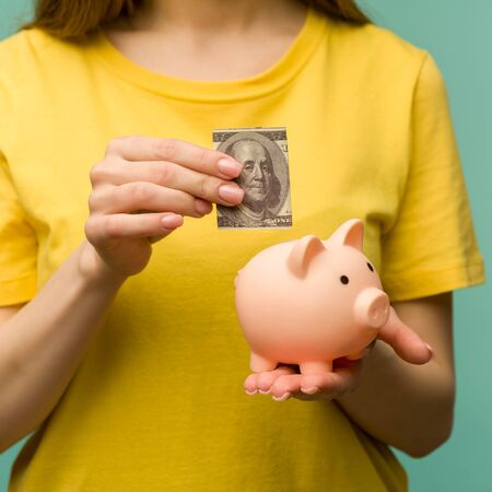 woman hand putting 100 dollars into piggy for saving money wealth and financial concept.- image Standard-Bild - 150222696
