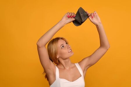 Young woman shows her empty wallet. Bankruptcy - image Standard-Bild - 150222702