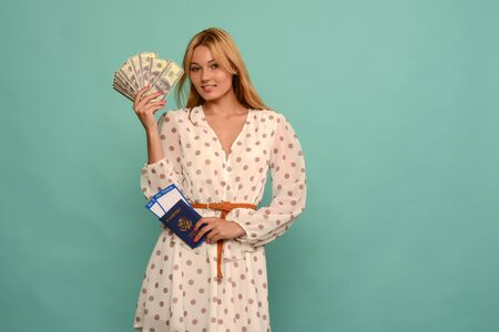 Cuty Young Woman Holding Tickets With Passport And Doller Money On Blue Studio Background - image Standard-Bild - 150222705