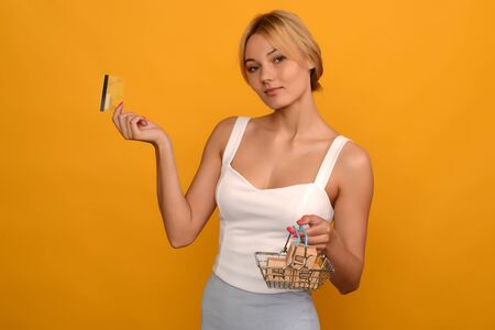 Young woman holds toy metal shopping basket with blue plastic handle and credit card isolated on background. image Standard-Bild - 150222708