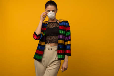 Beautiful slim girl fashion model posing in a protective respirator on a yellow background. LGBT community rainbow color jacket Stok Fotoğraf