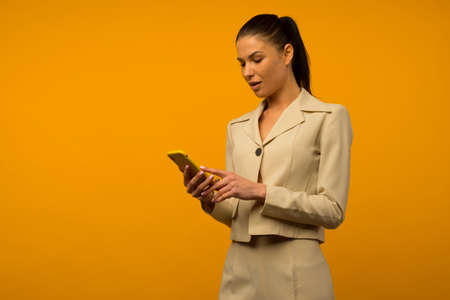 Young girl with facial skin problems posing with a smartphone on a yellow background. Banque d'images