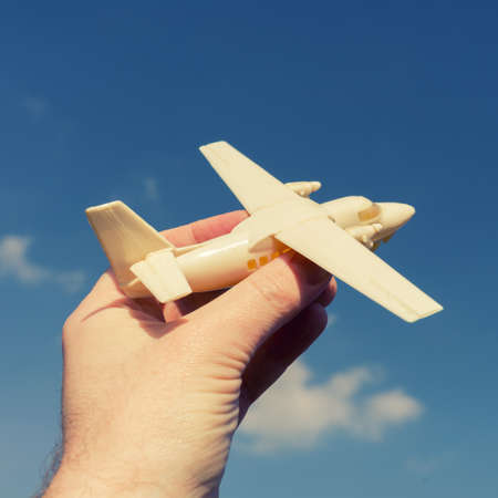 close up photo of male hand holding toy airplane against blue sky. image is retro filtered