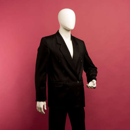 White male mannequin in a black business suit on a ruby background - image