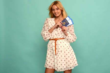 Joyful young woman in polka dot dress is holding airline tickets with a passport on a blue background. Rejoices in the resumption of tourism after the coronovirus pandemic.