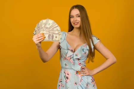 Joyful girl won the lottery and holds a fan of US dollars in her hands on a yellow background - image