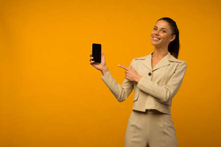 Young girl with facial skin problems posing with a smartphone on a yellow background. Standard-Bild