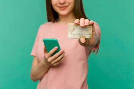 Photo of pleased happy screaming young woman posing isolated over blue wall background using mobile phone holding credit card. - image