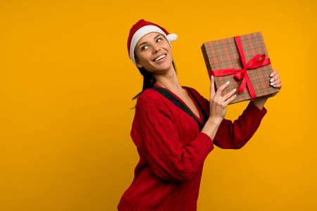 Happy excited young woman in santa claus hat with gift box over yellow background - image