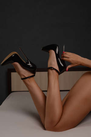 Beautiful female legs in a fetish shoe with extremely high heels. BDSM theme.