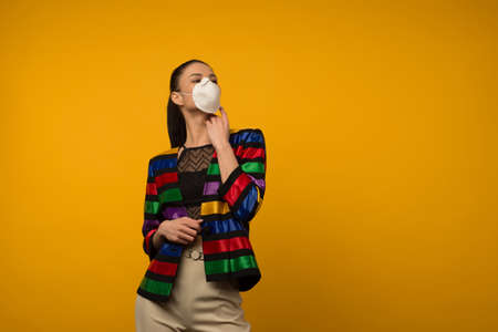 Beautiful slim girl fashion model posing in a protective respirator on a yellow background. LGBT community rainbow color jacket Standard-Bild