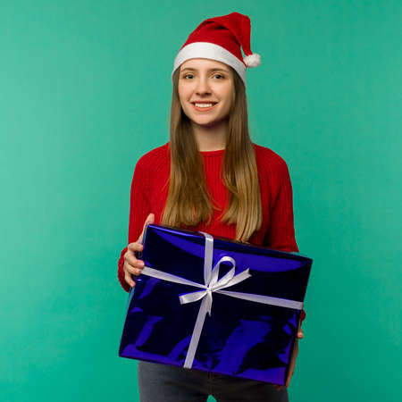 Happy excited young woman in santa claus hat with gift box over blue background - image