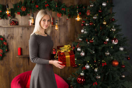 Beautiful young woman stands near a Christmas tree and holds a gift box in her hands in the New Year home interior. - image Standard-Bild
