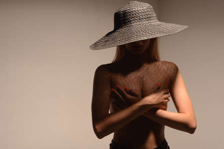 Beautiful young nude woman in a hat posing in the studio. - image