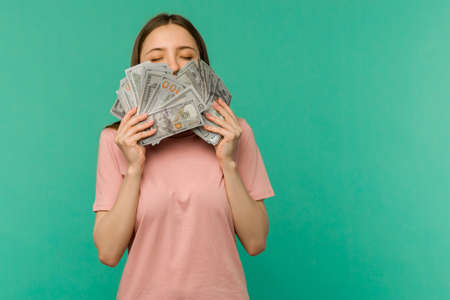 Portrait of a cheerful young woman holding money banknotes and celebrating isolated on blue background Standard-Bild