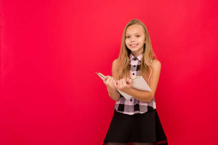 Lovely little girl standing and reading book over red background - image Standard-Bild