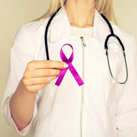 Female doctor in white uniform with purple awareness of ribbon in hand for ADD, ADHD, Alzheimer Disease, Arnold Chiari Malformation, Childhood Hemiplegia stroke, Epilepsy, Chronic Acute Pain, Crohns - Image Standard-Bild