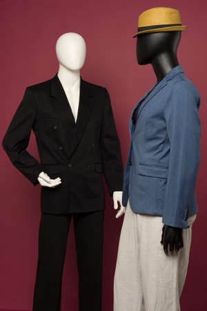 Two male mannequin in a black business suit and in a blue suit and white pants on a ruby background - image Standard-Bild