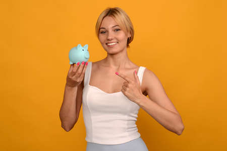 Beautiful young girl holding a pig piggy bank and pointing finger on yellow background. For saving money wealth and financial concept. image Standard-Bild