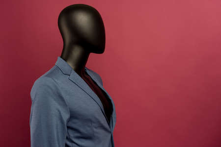 Black male mannequin in a blue suit on a ruby background - image
